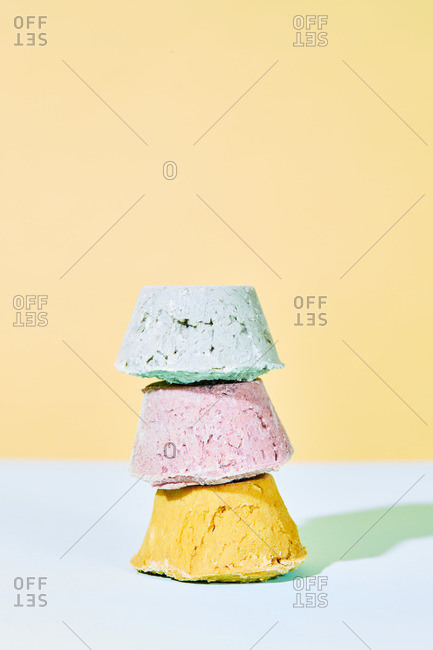 Heap of colorful handmade natural bath bombs staked on light background in studio