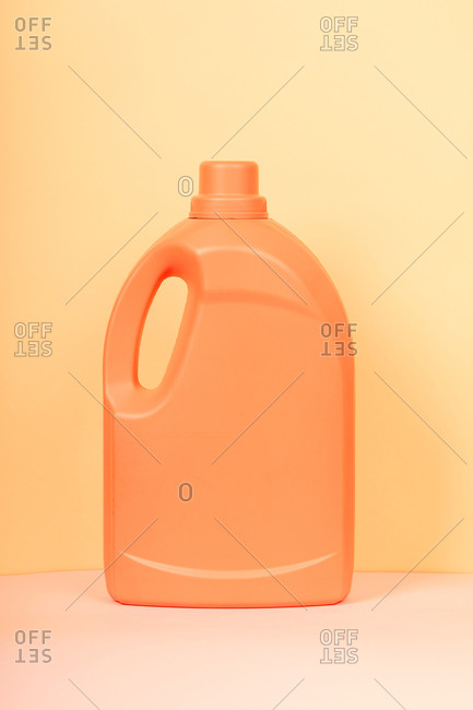 Bright plastic container from liquid detergent placed on vivid yellow background in studio