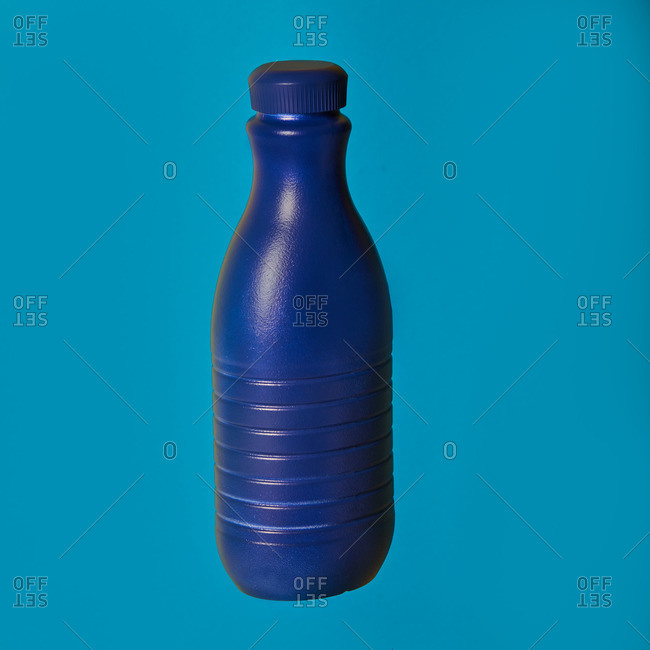 Blue plastic container from liquid detergent placed on vivid blue background in studio