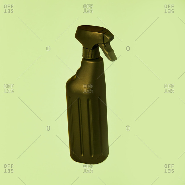 Black spray plastic container from liquid detergent placed on vivid pastel green background in studio