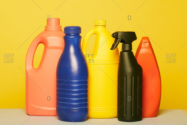 Set of colorful assorted plastic containers from liquid detergents placed in row on yellow background in studio