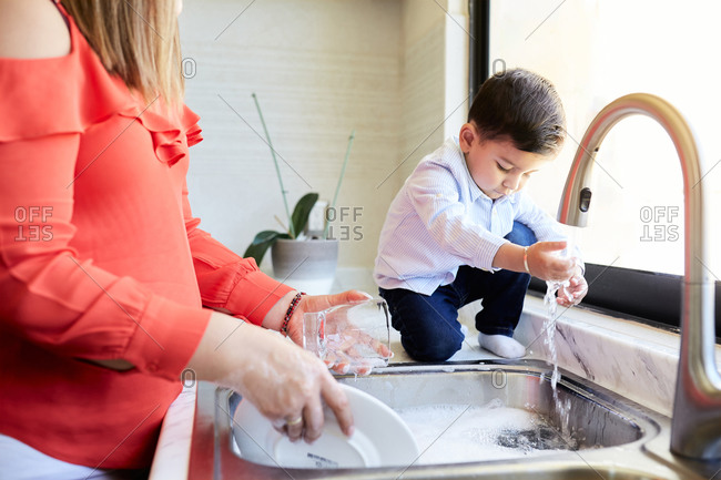 Delighted mother standing at sink in kitchen and washing dishes together with adorable little boy