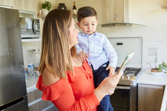 Hispanic woman with cute little boy standing in kitchen at home and browsing tablet while entertaining at weekend and talking