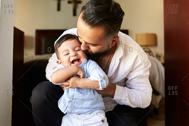 Delighted Hispanic father having fun with adorable little kid while spending time together at home