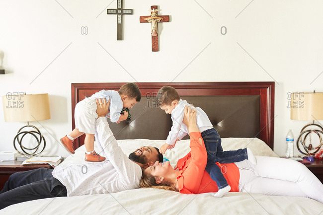Side view of Hispanic mother and father sitting on bed and playing with cute children in bedroom with religious crosses on wall