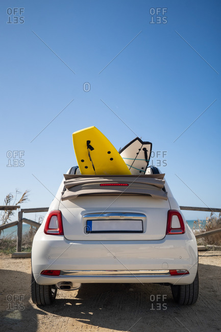 Modern white cabriolet automobile with surfboards parked on beach on sunny day in summer