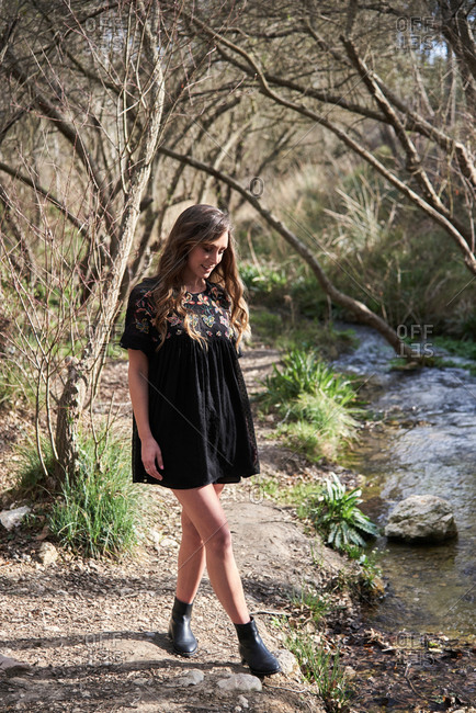 Carefree female wearing summer dress standing on shore of small brook in forest and enjoying nature on sunny day
