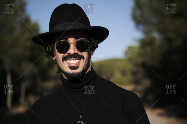 Side view of cheerful young hipster bearded male traveler with piercing wearing stylish black hat and sunglasses looking at camera while standing on blurred country road