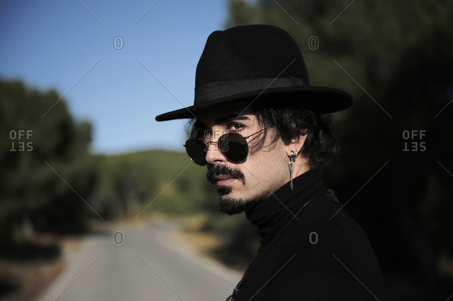 Side view of young hipster bearded male traveler with piercing wearing stylish black hat and sunglasses looking at camera while standing on blurred country road
