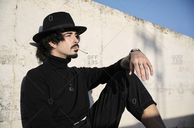 Side view of young bearded guy in stylish black clothes and hat smoking cigarette and looking away thoughtfully while sitting near shabby concrete wall on street