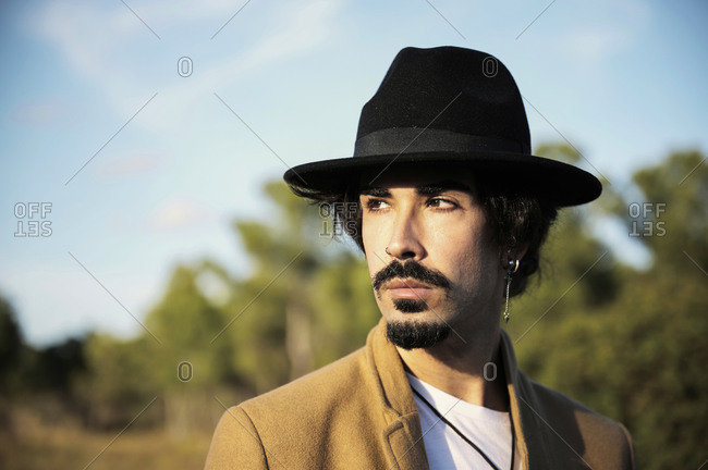 Young stylish hipster bearded male traveler with piercing wearing black hat looking away while standing on blurred countryside