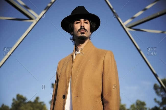 From below of confident young ethnic male in stylish coat and hat looking at camera while standing against high metal electric tower and blue sky