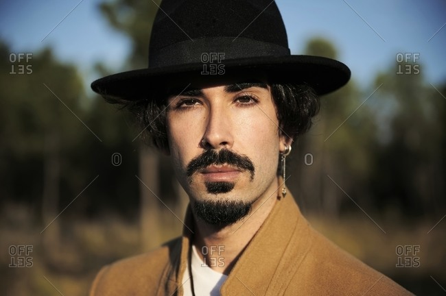 Young stylish hipster bearded male traveler with piercing wearing black hat looking at camera while standing on blurred countryside