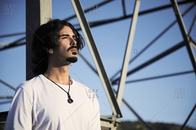 Side view of young bearded male traveler in trendy clothes leaning back against metal pole and looking away while spending sunny autumn day in field