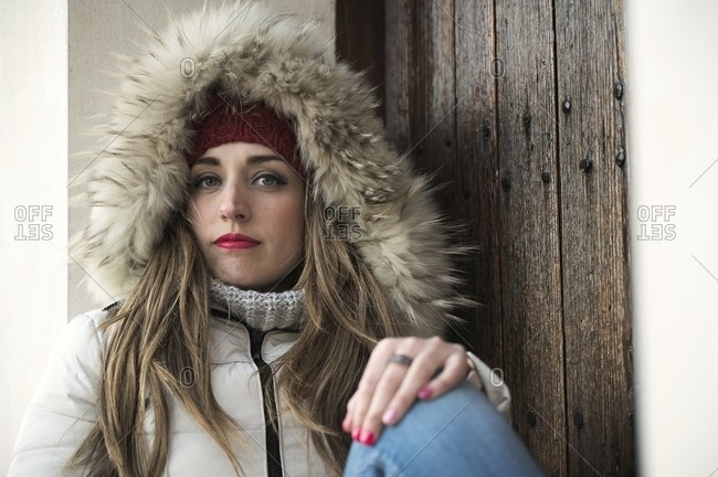 Tranquil female wearing warm winter jacket and knitted hat sitting near wooden door in city and looking at camera