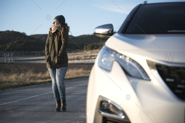 Content female in warm clothes standing on roadway near automobile and enjoying sunny day with closed eyes