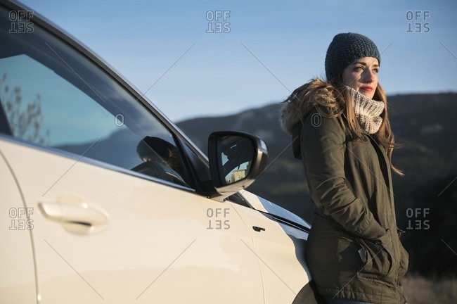 Content female in warm clothes standing on roadway near automobile and enjoying sunny day looking away