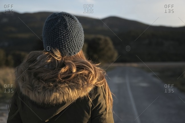 Back view of unrecognizable traveling woman in warm outerwear standing on empty roadway and enjoying view of mountainous landscape
