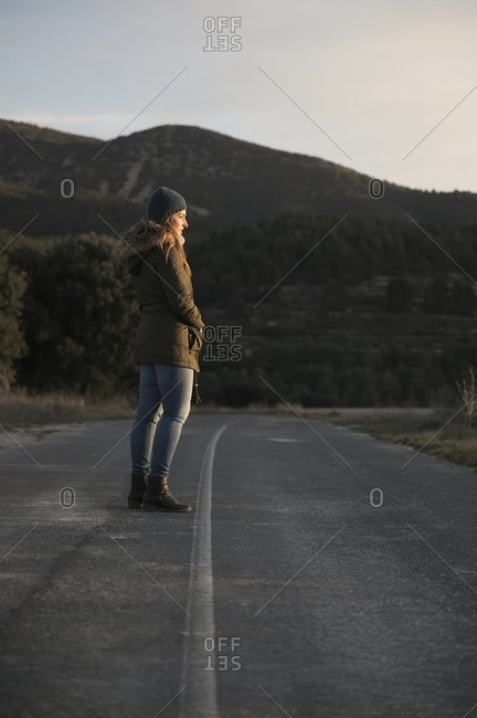 Side view of traveling woman in warm outerwear standing on empty roadway and enjoying view of mountainous landscape