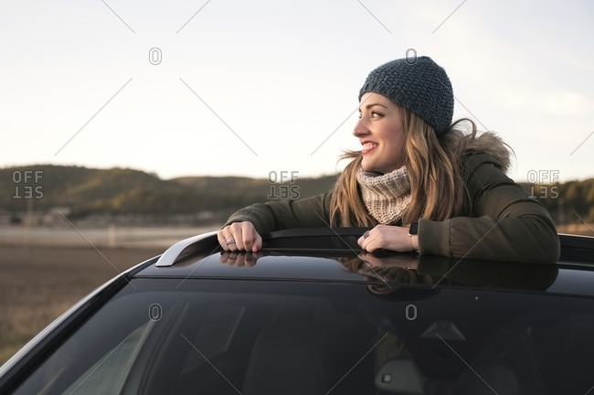 Cheerful female in warm clothes standing out of car sunroof and admiring amazing natural scenery during road trip