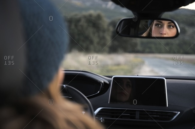 Female traveler sitting on driver seat during road trip along roadway in highlands in cold season
