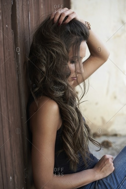 Side view of calm female sitting near old weathered building and touching long wavy hair while relaxing and looking down