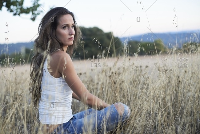 Side view calm slim brunette with long hair sitting alone on meadow in countryside looking away in dreams
