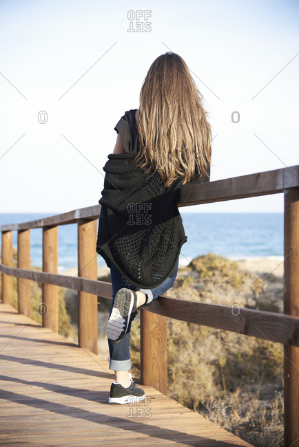 Back view of unrecognizable calm brunette in cozy sweater with long hair standing at on wooden promenade the beach