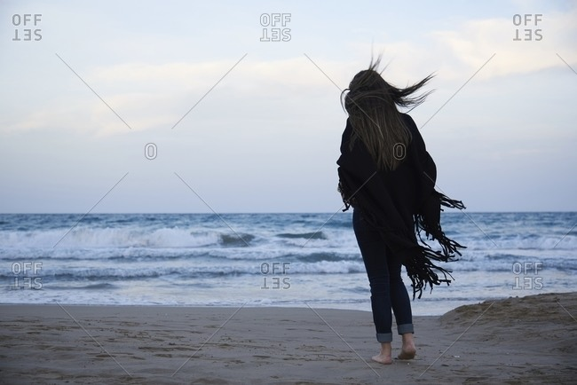 Back view of barefoot woman in shawl standing on sandy coast against wavy ocean