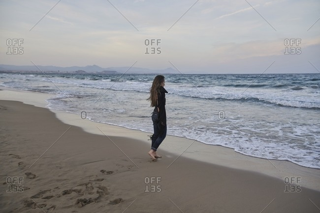 Side view of barefoot woman in shawl standing on sandy coast against wavy ocean