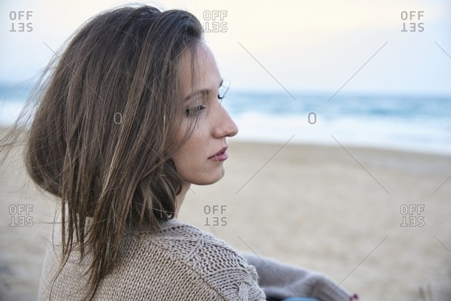 Side view of peaceful thoughtful female in casual clothes standing on sandy meadow in rural area and looking away