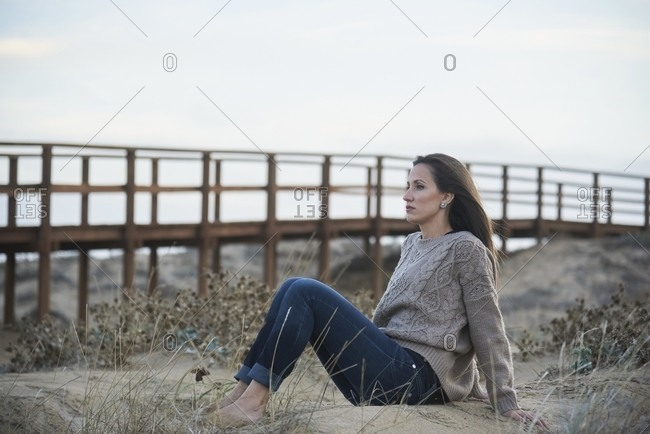 Full length female in cozy sweater and denim sitting barefoot on seashore with boardwalk and looking away