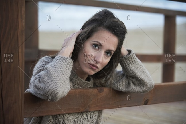 Calm brunette in sweater sitting on wooden promenade and leaning on fence looking at camera