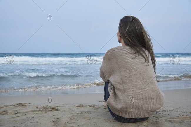 Back view of unrecognizable female sitting on sandy shore and admiring amazing view of sea in evening