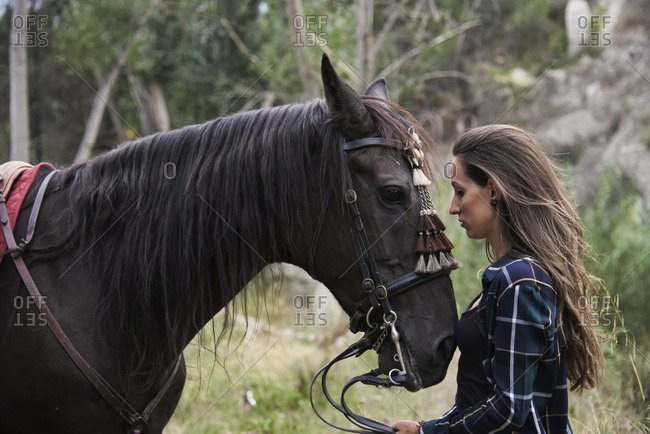 Side view of tranquil female equestrian caressing muzzle of chestnut horse while standing in woods and looking at each other