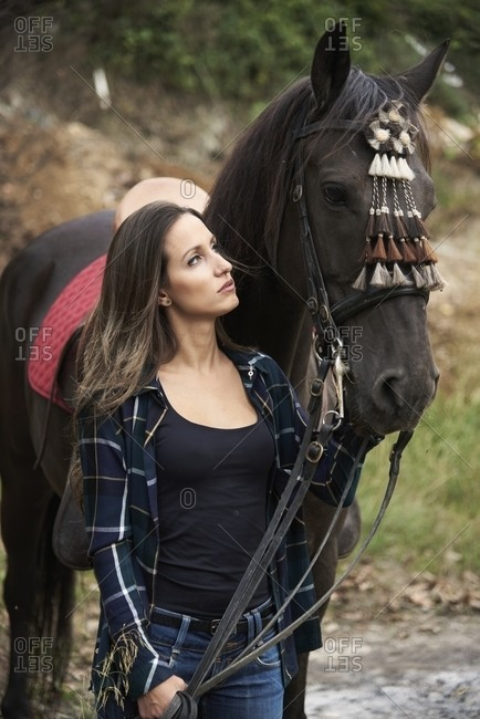 Tranquil female equestrian caressing muzzle of chestnut horse while standing in woods and looking at each other