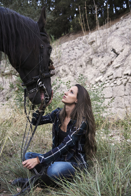 Side view of loving female equestrian tenderly kissing muzzle of chestnut horse in harness in forest