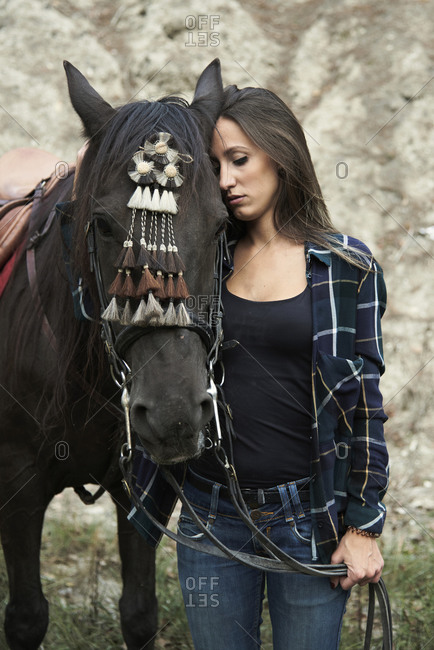 Peaceful female equestrian hugging chestnut horse in bridle while standing in nature and closed eyes