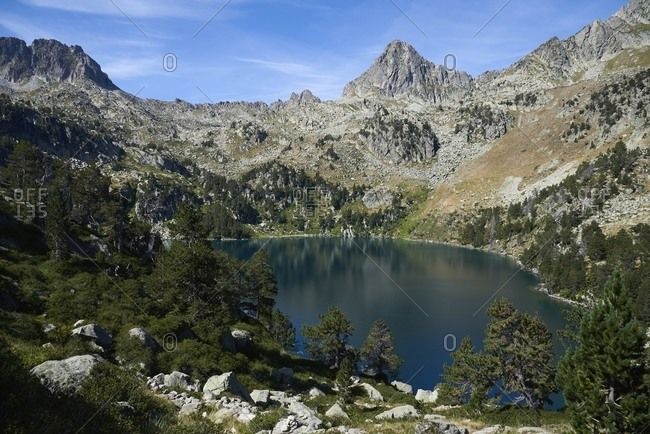 Rocky mountains and blue sky reflecting in smooth surface of calm pond in highland area in Estany Gerber in Lleida, Spain
