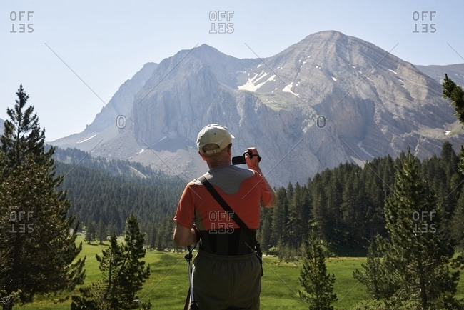 Back view of unrecognizable mature male tourist standing in highlands and taking pictures of magnificent mountain range in summer during vacation
