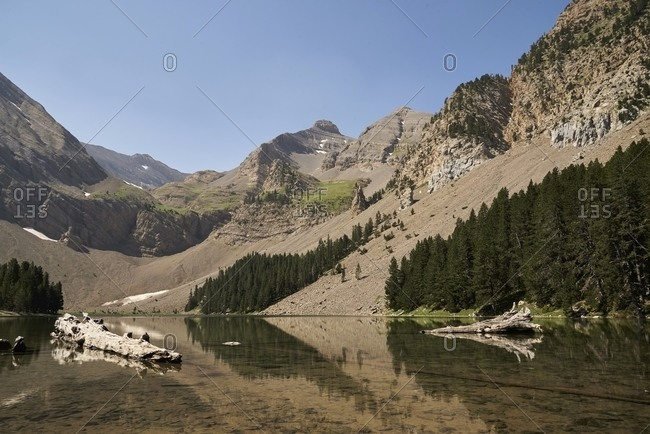 Scenery of calm pond with clean water near mountains under blue cloudless sky on sunny day
