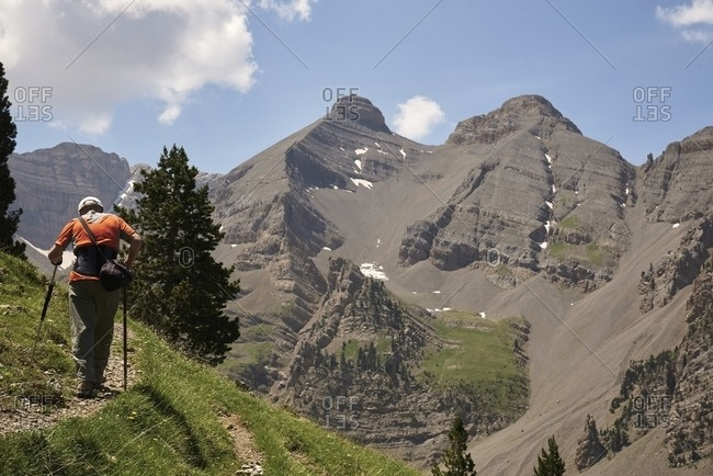 Back view of mature male hiker walking along path with trekking poles in highland terrain during vacation in summer