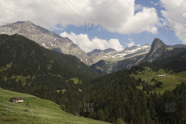 Breathtaking view of green mountain range covered with forests and located in Barrosa cirque