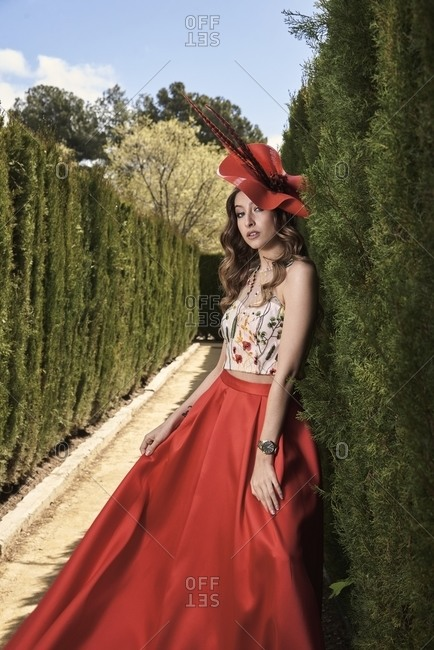 Side view of young graceful female wearing fancy hat and long skirt standing in lush garden and charmingly looking at camera