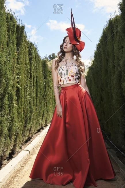 Young graceful female wearing fancy hat and long skirt standing in lush garden and charmingly looking away