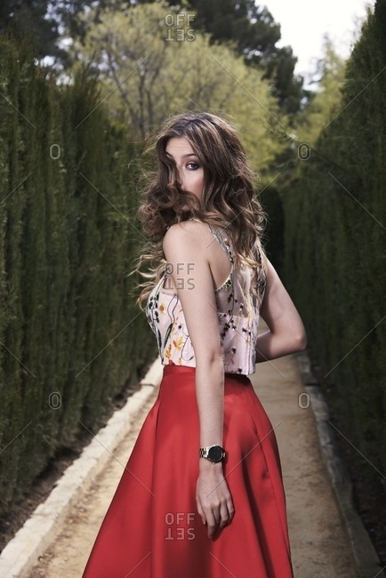 Back view of graceful female with long wavy hair and in stylish dress walking along path in garden and looking at camera over shoulder