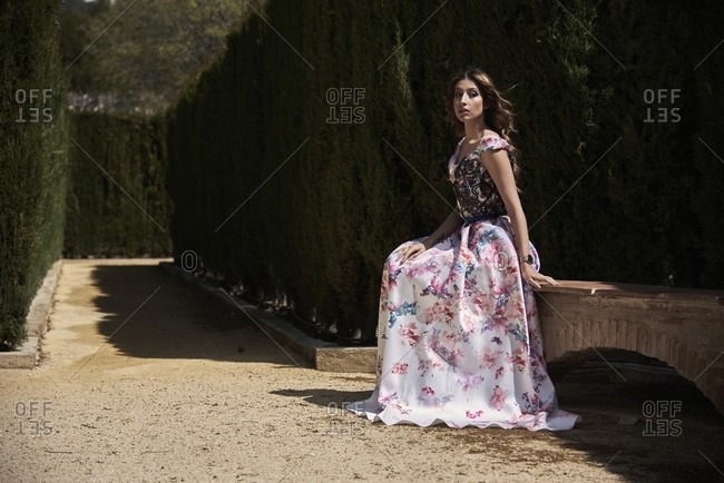 Side view of graceful female wearing maxi elegant dress sitting on stone bench in park and looking calmly at camera
