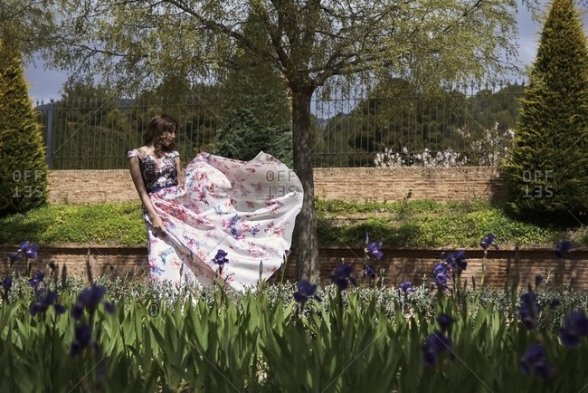 Graceful young female in long elegant dress spinning around in garden on sunny day