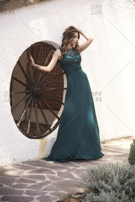 Slender female with long hair and in elegant emerald dress standing near old building in ancient town