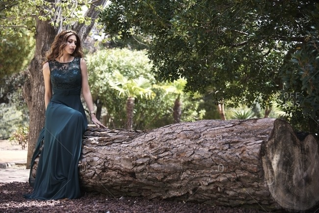 Full body of dreamy female wearing maxi emerald dress sitting on tree trunk in woods and looking down